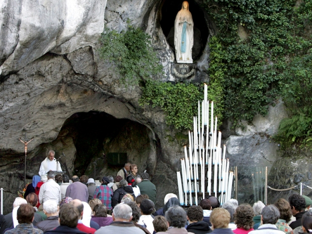 Pilgrims pray in front of Lourdes grotto, the site where the Roman Catholic tradition says St. Bernadette saw visions of Mary in 1858, during the plenary congress of France's Bishops in Lourdes, southwestern France, November 5, 2006. REUTERS/Regis Duvignau (FRANCE) - RTR1J1AW