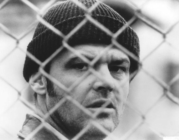 one-flew-over-the-cuckoos-nest-1975-006-jack-nicholson-beanie-hat-behind-wire-black-white-bfi-00m-tco
