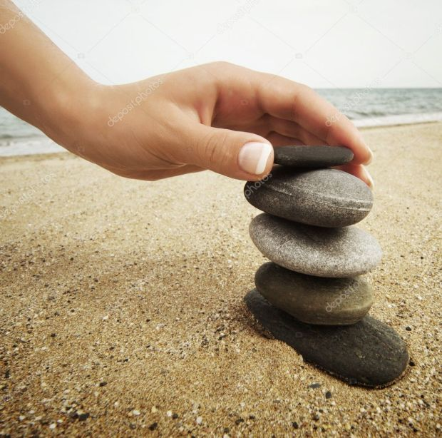 depositphotos_6229482-woman-hand-touching-stones-on-the-beach
